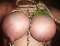 乳房をロープで縛られた乳首ピアスをした女性