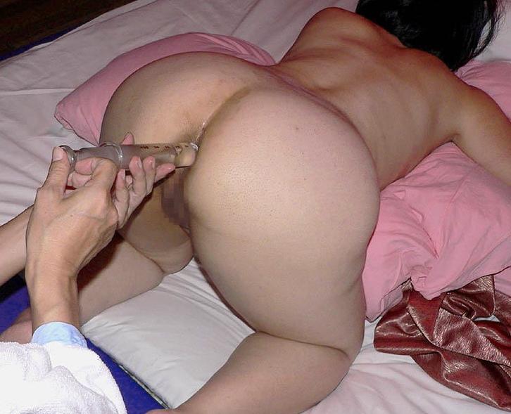 浣腸器で浣腸液を注入されている女性
