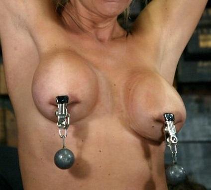 乳首クリップをつけて錘がが乳房からぶら下がっている女性