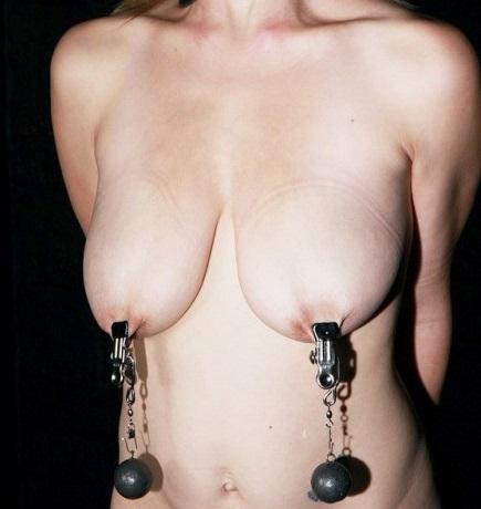 乳首クリップをつけて錘が乳房からぶら下がっている女性