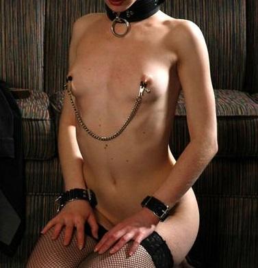 乳首クリップをつけてチェーンが乳房からぶら下がっている女性