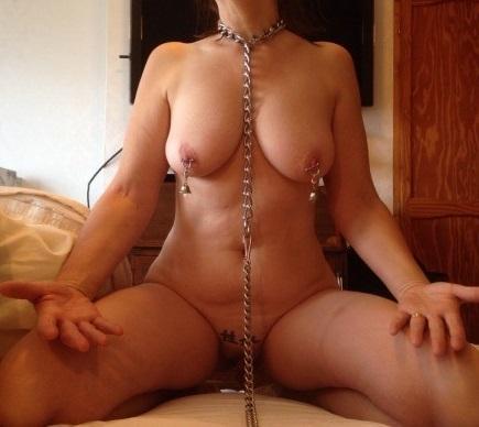 乳首クリップをつけてベルが乳房からぶら下がっている女性